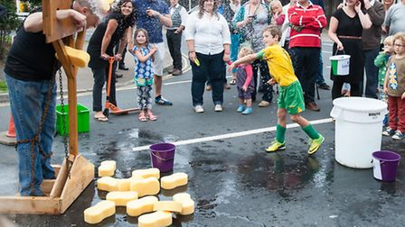 Trafford Arms landlord Chris Higgins is led to the stocks and doused. Photo: Bill Smith