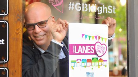Duane Dibartolomeo, Grosvenor Fish Bar co-owner, puts up a support poster for the Norwich Lanes. Pic