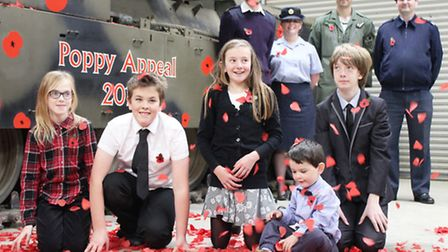 Norfolk service men and women's youngsters are showered with poppy petals, dropped from a retired Ch