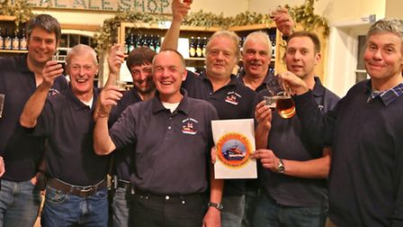 Members of the Wells RNLI crew with Teddy Maufe at The Real Ale Shop toasting the winning ale. Pictu