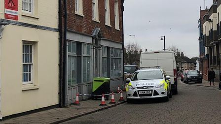 A police cordon and police car outside a building