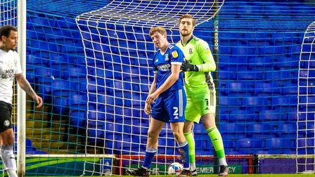 Ipswich keeper Tomas Holy helps a crestfallen Mark McGuinness to his feat after he had put the ball