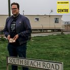 A man holds the medal in behind a road sign