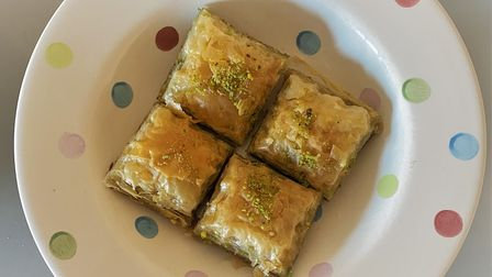 Baklava dessert topped with chopped pistachio nuts
