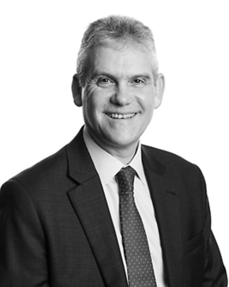 Black and white photograph of a smiling and professional solicitor looking at the camera