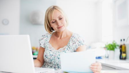 Woman sitting at kitchen table with laptop open looking at paperwork