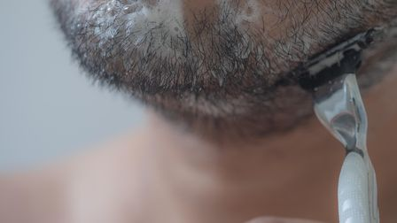 Man is shaving beard his face in bathroom in morning. Close up