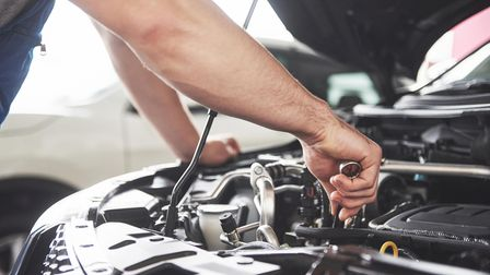 Close up hands of unrecognizable mechanic doing car service and maintenance.