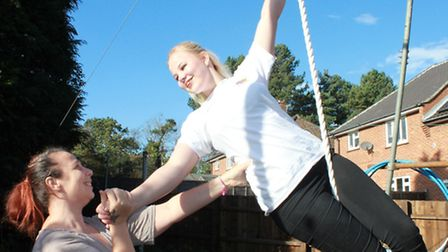 Sixteen-year-old Lucinda Young practising her aerial act on her back garden trapeze with the help of