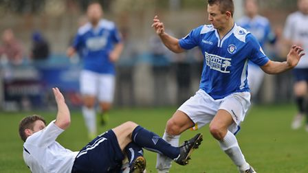Jake Lawlor of Guiseley A.F.C slides in on Jake Reed of Lowestoft Town during the Conference North m
