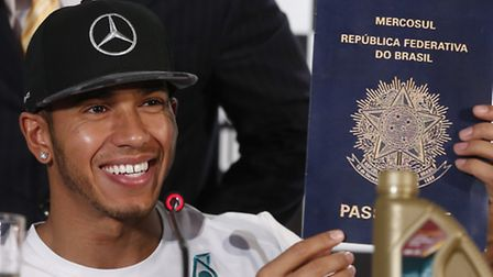Mercedes driver Lewis Hamilton holds up an oversized, mock Brazilian passport given to him by TV com