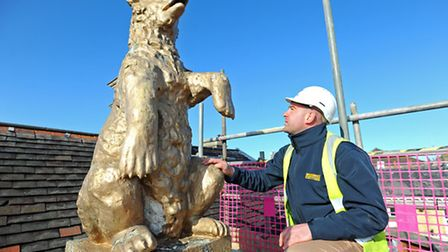 Construction manager Phil Munnings up close with one of the bears on top of the former Two Bears Hot