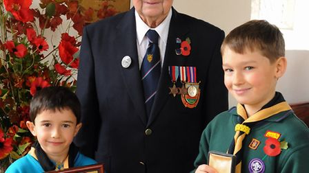 Normandy veteran, David Woodrow, and his grandsons, James, 6,, left, and William, 9; holding a photo