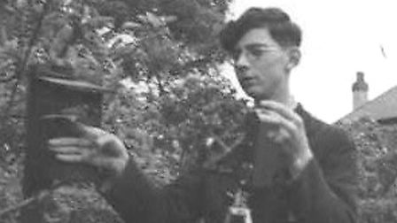 This 1949 photo shows an ornithologist photographing a nest box.