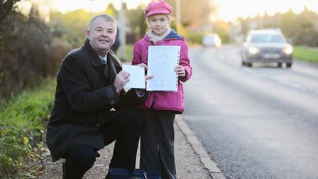 Amie Adams (8) hands over the road safety petition to Tom McCabe at the Poppyfields crossing, West L