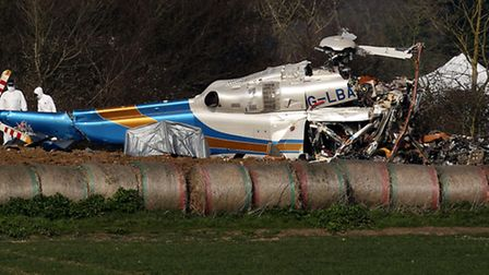 File photo dated 14/03/14 of forensic officers examining the wreckage of the helicopter crash. Photo