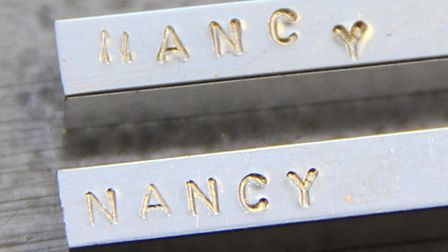 David Cameron's attempt at engraving his daughter's name, top, with a professional version below.