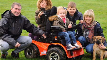 May Haughan-Zelos, 4, in her new electric wheelchair, with her family, mum Emily Haughan, and dad Gr