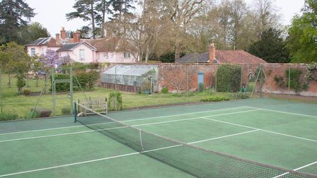 Green hard standing tennis court in front of a large pale pink country house
