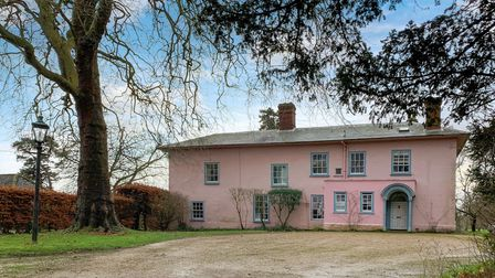 Period home painted in a Suffolk pink colour wash with a large shingle driveway in front, and a large tree