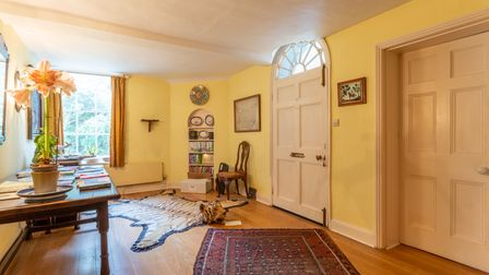 Large entrance hall painted yellow with a tiger rug on the wooden floor and a bright window letting in lots of light in the distance