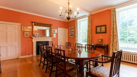 Large formal dining room featuring a large wooden dining table in the centre with eight chairs and a chandelier hanging from the ceiling