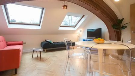 Modern open-plan living area with two sky lights and a stone archway