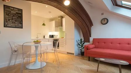Open-plan living area featuring historic stone archway leading through to a modern white fitted kitchen