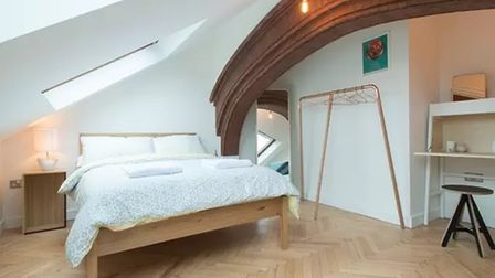Double bedroom painted white with a double bed in the centre under a skylight and a historic stone archway
