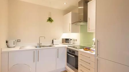 Modern kitchen with base and wall units featuring an electric oven and hob with a sink and drainer