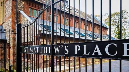 Exterior shot of a wrought iron gate reading 'St Matthew's Place' with a brick and stone building behind it