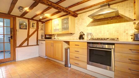 The kitchen complete with wood beams and stone flooring.