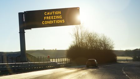 Motorway gantry sign in early morning winter sunshine reading caution freezing conditions