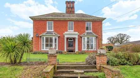 Photograph of a large Victorian country home with two bay windows and a large garden at the front