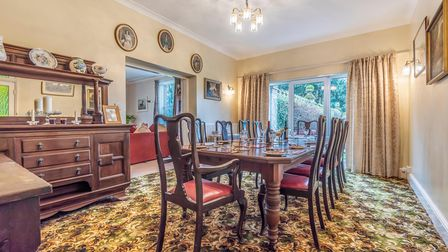 Formal dining room with large dining table in the centre, patio doors overlooking the garden and a chandelier hanging from the ceiling