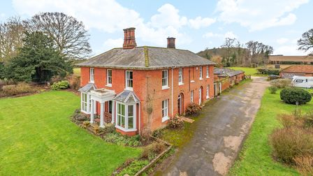 Exterior photograph of a large Victorian country house with hard standing area providing ample off road parking and bright green lawns