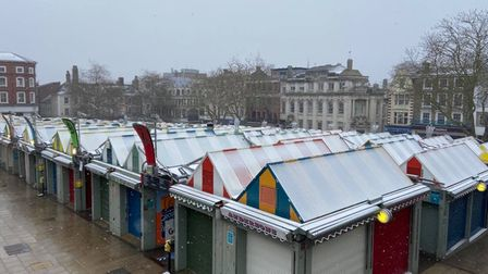 A light dusting of snow settling on the top of striped stalls at Norwich Market.