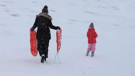 A family sledging in the snow inWoodbridge