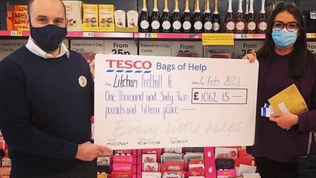 Mark South andJenny Canhan with a cheque from book sales at Dereham's Tesco Extra donated to Litcham FC.