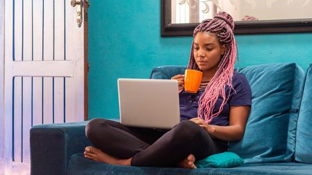 Young woman sitting on a sofa with a laptop and hot drink