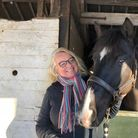 Woman standing at stable with horse