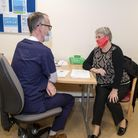 Picture of a doctor and patient in a room discussing the Covid-19 vaccine