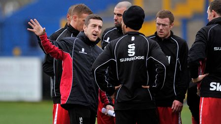 Brackley Town manager Jon Brady gives instructions to his players during the warm-up