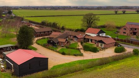 Aerial photograph of four detached linked barns in countryside surrounded by a sweeping shingle lawn