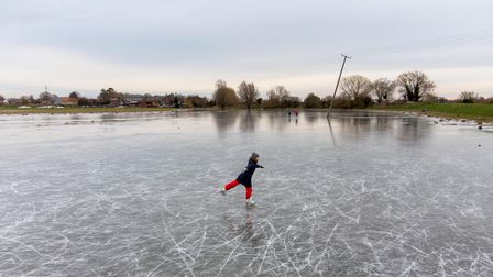 People ice skate on frozen flooded fields near Ely in Cambridgeshire, as the cold snap continues to