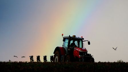 A rainbow colours the sky over a farmer as he ploughs a field near North Walsham.Picture: ANTONY KEL