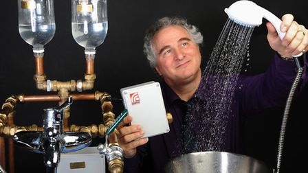 Alan Wright, director of Wrightsolar, holding the shower power booster (grey box) he has designed. P