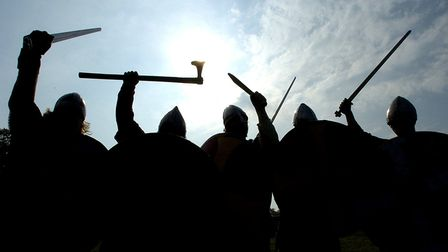 The silhouettes of Saxon warriors preparing for battle.