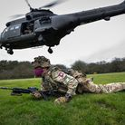 A member of The 3rd Battalion, The Parachute Regiment, gets in the prone position after disembarking