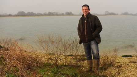 Jamie Lockhart, farm manager at Honingham Thorpe Farms, with the farm's reservoir. Picture: DENISE B